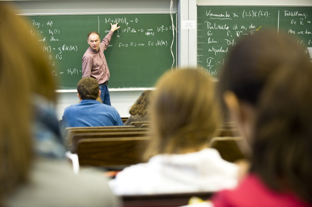 Classroom, with a teacher pointing at something on the board
